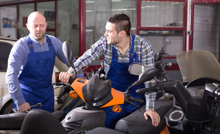 Two car mechanics inspecting motor bikes at workshop photo