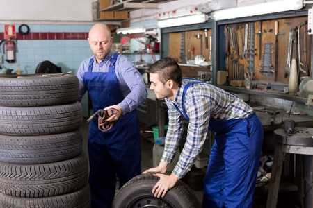 specialists: Happy adult mounting specialists working at auto repair shop. Focus on the right man Stock Photo