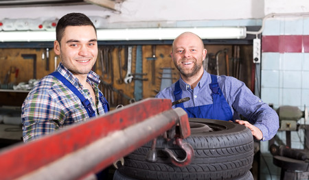 mounting holes: Happy adult mounting specialists in coveralls working at auto repair shop Stock Photo