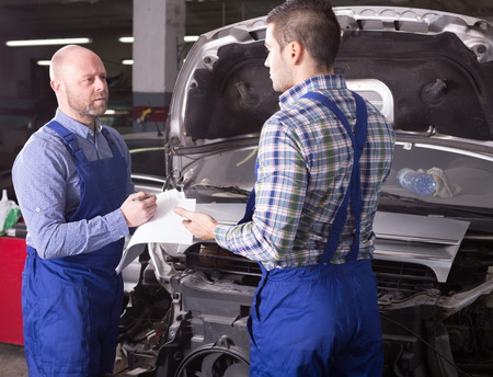 journeyman: Workman calculating the cost of work in the auto repair shop