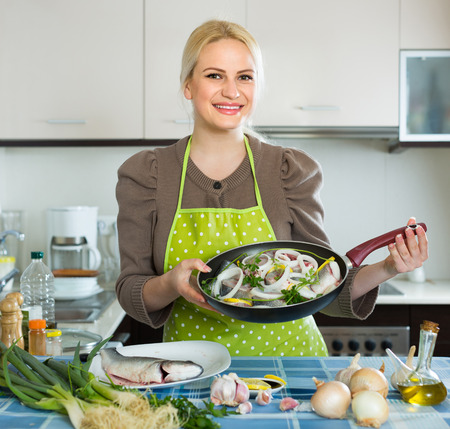 cheeful: Happy housewife cooking fish with lemon at home kitchen