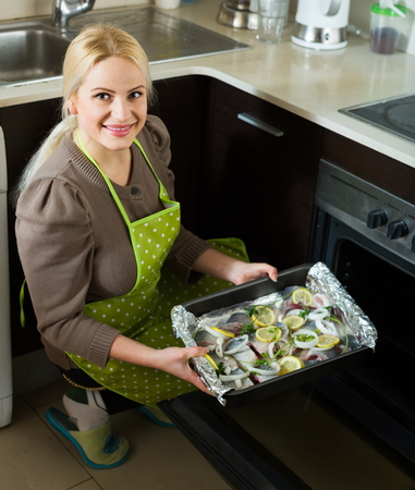 fryingpan: Smiling woman cooking fish  in oven at home kitchen