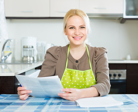 contractual: Happy woman sitting at kitchen and signing contractual agreement for renting new flat