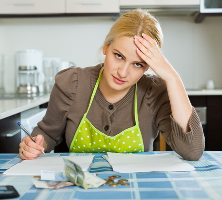 ruminate: Blond housewife filling in utility payments bills at  home