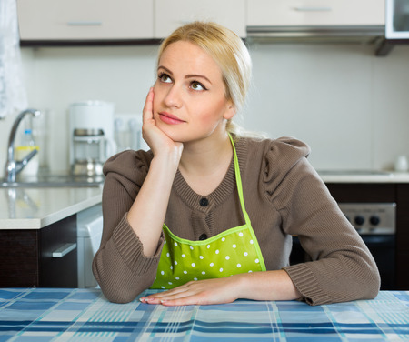 heartbreak issues: Lonely sad blonde young woman sitting at kitchen Stock Photo