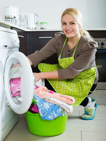 stereotypical: Home laundry. Smiling american  girl using washing machine at home