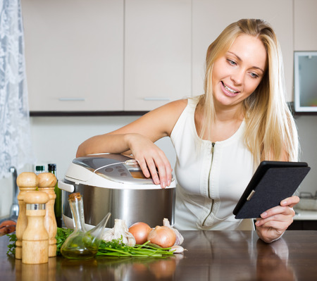 ereader: Blonde smiling girl reading ereader while with new electric multicooker doing food at home Stock Photo