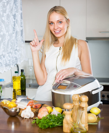 Smiling blonde housewife cooking salmon with new electric multicooker at home photo