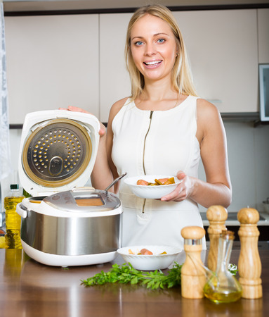 slow cooker: Young long-haired housewife cooking with new electric multicooker at home Stock Photo