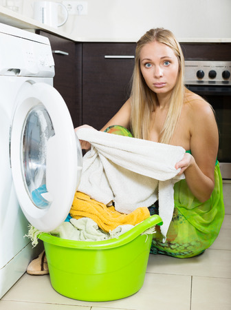 unsound: Unhappy  housewife with  clothes near washing machine at  home
