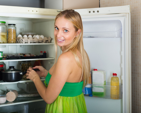 parsimony: serious  girl with money and documents in home kitchen