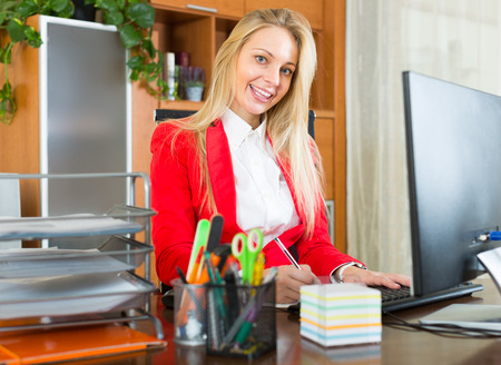 habitual: Young smiling businesswoman with documents working in office room Stock Photo