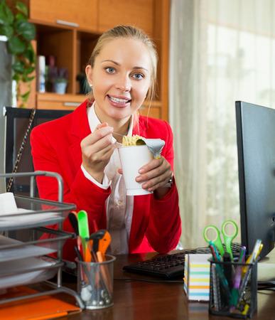 overworking: Young blond woman in jacket having breakfast in office