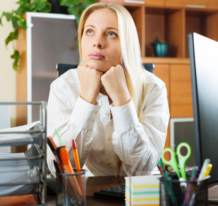 unbearable: Bored   woman in white dreaming at office desk
