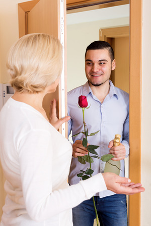 sympathetic: sympathetic son with gifts visiting senior mother at her place Stock Photo