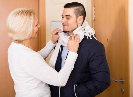 mamma e figlio: Felice senior madre aiutare figlio adulto a legare una sciarpa
