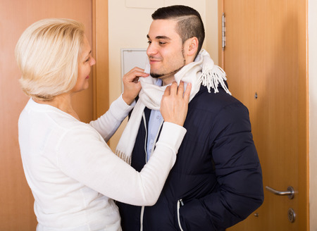 madre e hijo: Madre senior feliz ayudando a hijo adulto atar una bufanda