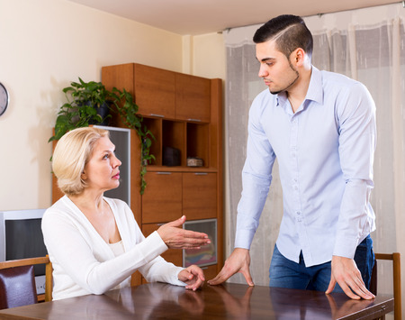 Sad guy and his mature girlfriend having serious conversation indoors