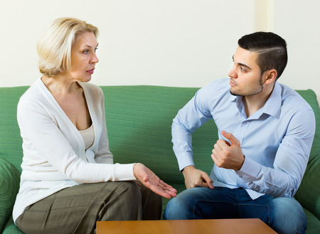 Aged woman and young guy discussing something with serious faces on sofa Stock Photo