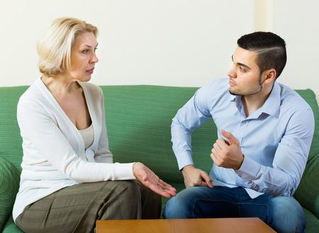 Gealterte Frau und junger Mann diskutieren etwas mit ernsten Gesichtern auf dem Sofa