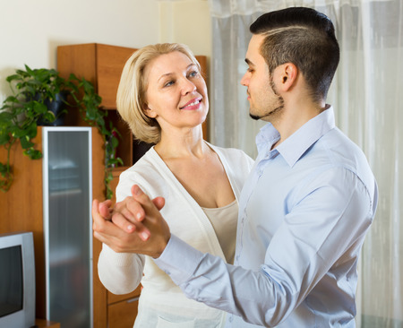 mismatch: Young man and senior woman slowly dancing and smiling indoor