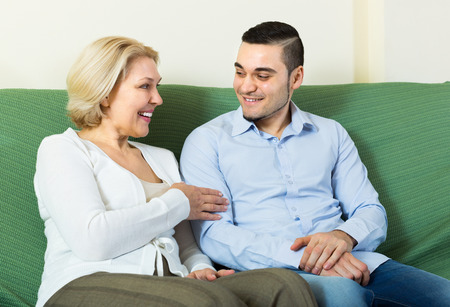 Positive smiling mature woman chatting with young boyfriend indoors