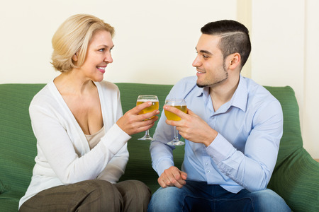 mismatch: Handsome guy and mature woman drinking wine and smiling Stock Photo