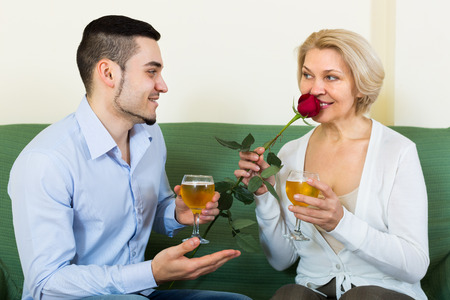 congratulating: Adult son congratulating smiling mother and proposing a toast. Focus on guy