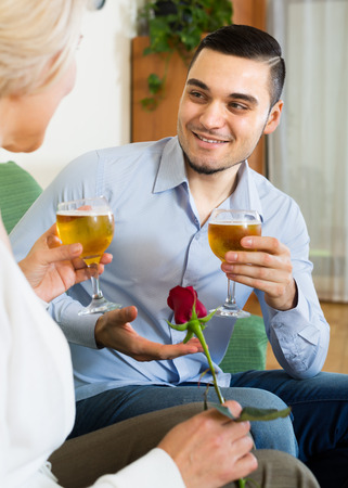 mismatch: Young guy and elderly blonde woman drinking wine and smiling indoor