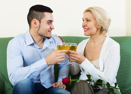 mismatch: Handsome guy and elderly woman drinking wine and smiling Stock Photo