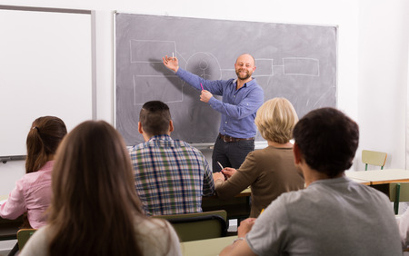 lecture: Attentive adult students with teacher in classroom