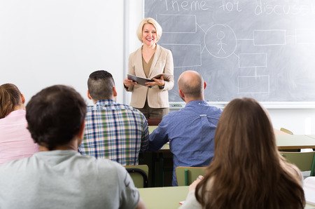 student desk: Smiling female teacher lecturing adult students in a university