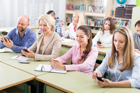 normal school: Professionals with smartphones at training session for employees. Focus on girl