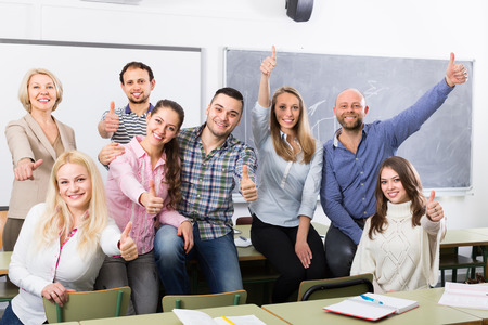 cohesive: Cheerful smiling adult students and coach posing at training session school. Selective focus