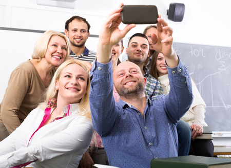 cohesive: Professor creating a selfie with his students in a classroom Stock Photo