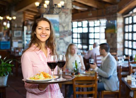 Portrait des adultes souriants ayant le dîner et le serveur respectueux Banque d'images