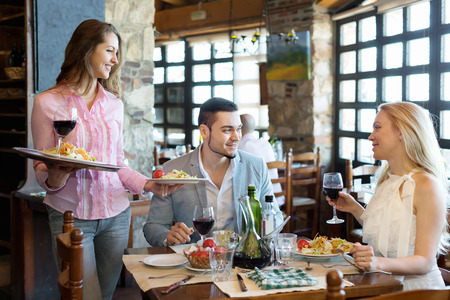 respectful: Portrait of smiling  adults people having dinner and respectful waiter