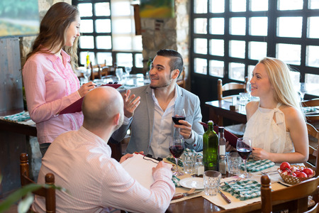european people: Cheerful waitress taking the order from visitors sitting at the table in a restaurant Stock Photo