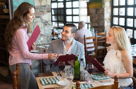 camarero: Alegre hembra joven sonriente camarero sirve a sus hu�spedes restaurante. Enfoque selectivo Foto de archivo