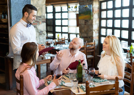 respectful: Relaxed adults people having dinner and respectful waiter Stock Photo