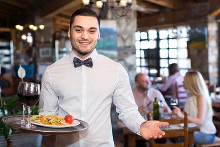 mesero: Feliz sonriente apuesto camarero en un restaurante con una bandeja con un Saland y vasos llenos de vino en un restaurante Foto de archivo