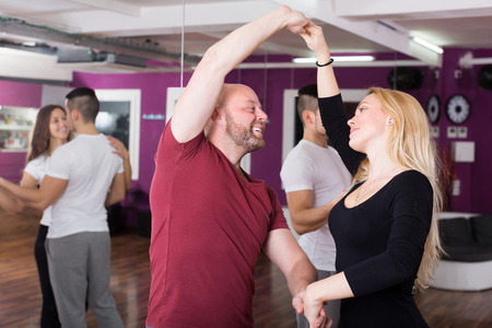 Cheerful couples enjoying of partner dance indoor Stock Photo