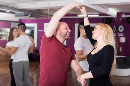 unprofessional: Cheerful couples enjoying of partner dance indoor Stock Photo
