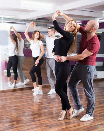 dancing club: Positive couples enjoying of partner dance and smiling indoor