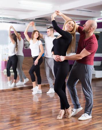 taniec: Pozytywne pary korzystających z partnerem taniec i uśmiecha się kryty