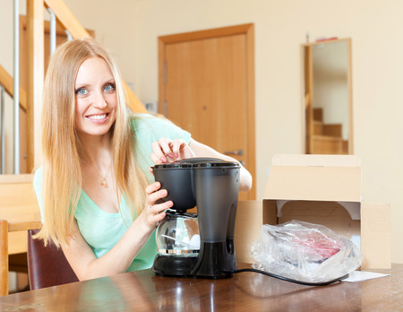 Happy young woman with new coffee machine at home in living room Stock Photo