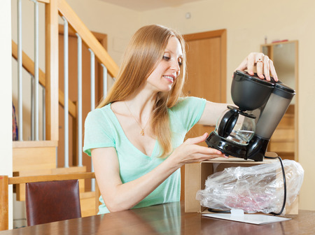 coffeemaker: cheerful woman unpacking and reading manual for new coffeemaker at home interior