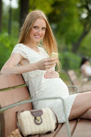 gravida: Smiling pregnant woman using mobile phone in  summer park