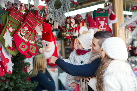 Happy family choosing Christmas decoration at Christmas market photo