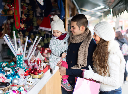 A handsome man with his baby girl and beautiful wife are buying christmas tree decorations. photo